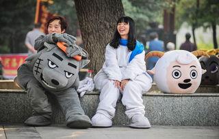"""10月6日,洛阳市王城公园,扮演""""喜羊羊""""与""""灰太狼""""的卡通人偶演员坐在一起休息新华社"""