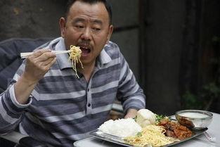 潘长江在自家小院吃盒饭。