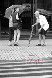 9月1日,在广州北京南路,有位行动缓慢的91岁老伯,他每天拄着一把雨伞过马路十分引人注目,但基本无路人帮扶,交通协管员亦称每次搀扶老人过马路前内心都十分挣扎.